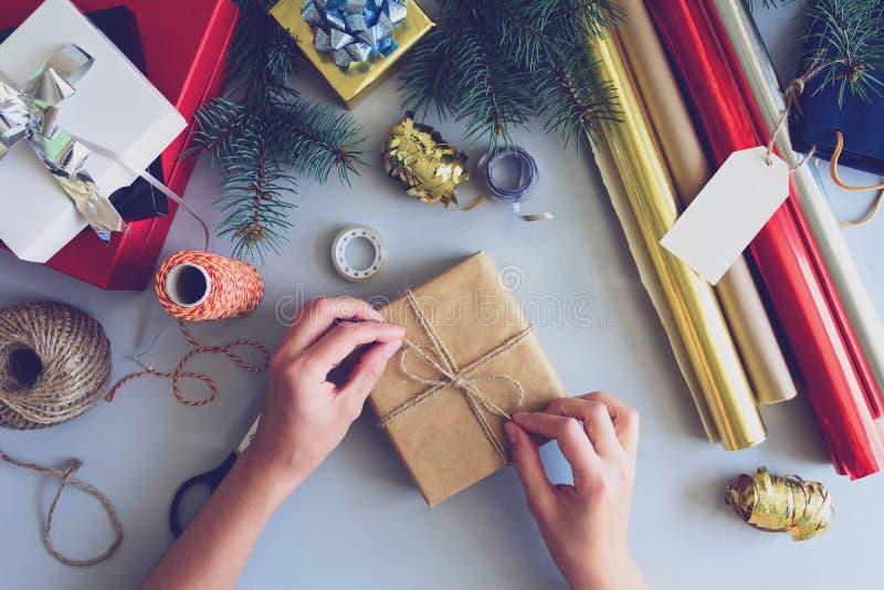Τα χέρια γυναικών ` s διακοσμούν το παρόν κιβώτιο στο γκρίζο ξύλινο υπόβαθρο Νέα έννοια διακοσμήσεων έτους και Χριστουγέννων στοκ φωτογραφία με δικαίωμα ελεύθερης χρήσης