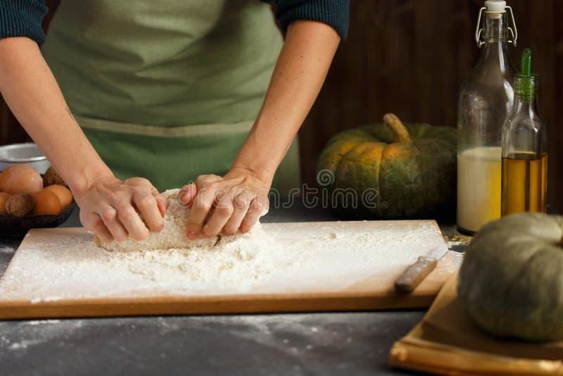 Τα χέρια γυναικών ` s ζυμώνουν τη ζύμη Συστατικά ψησίματος στον ξύλινο πίνακα στοκ εικόνες
