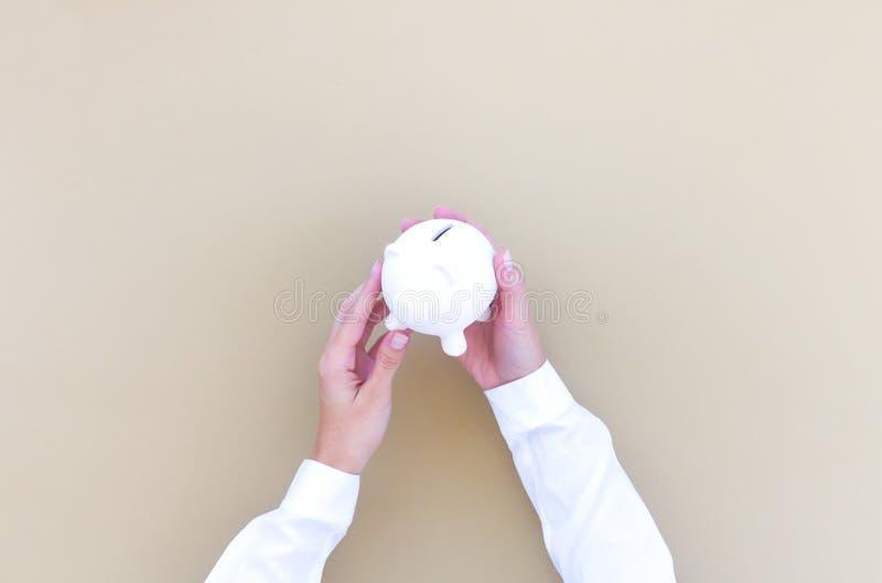 Τα χέρια γυναικών ` s κρατούν μια piggy τράπεζα στοκ φωτογραφία