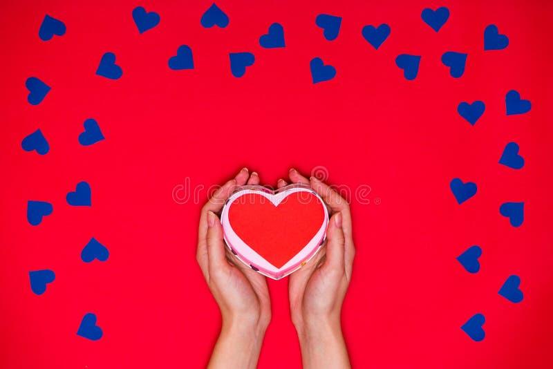 Τα χέρια γυναικών ` s κρατούν την κόκκινη καρδιά στο κόκκινο υπόβαθρο στοκ εικόνα με δικαίωμα ελεύθερης χρήσης