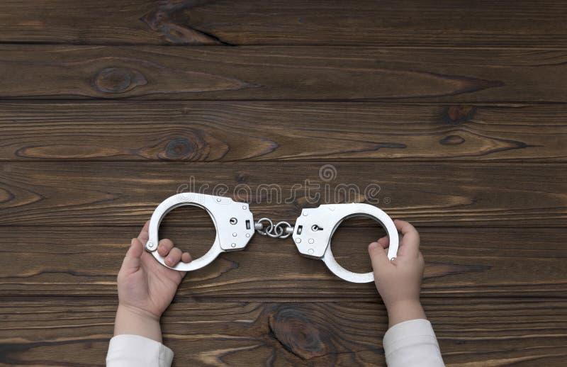 Τα χέρια δένονται με χειροπέδες σε ένα ξύλινο υπόβαθρο έγκλημα παιδιών στοκ φωτογραφίες με δικαίωμα ελεύθερης χρήσης