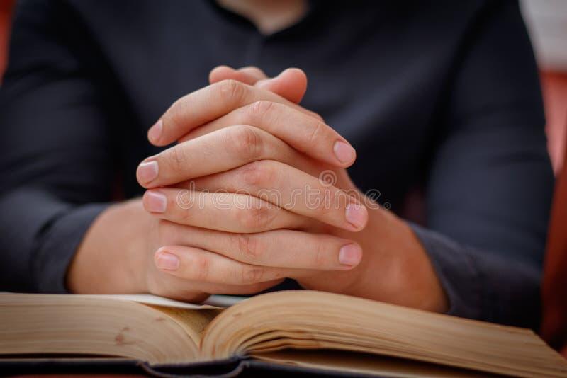 Τα χέρια δίπλωσαν στην προσευχή σε μια ιερή Βίβλο στην έννοια εκκλησιών για την πίστη, το spirtuality και τη θρησκεία στοκ φωτογραφίες με δικαίωμα ελεύθερης χρήσης