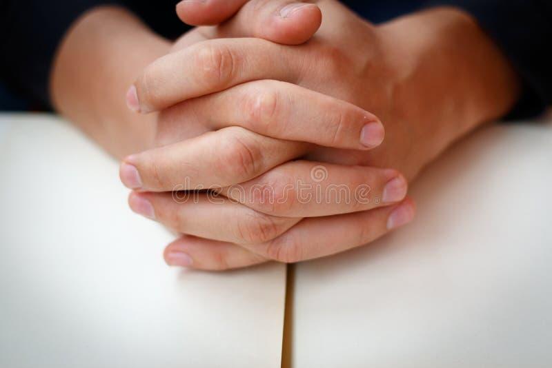 Τα χέρια δίπλωσαν στην προσευχή σε μια ιερή Βίβλο στην έννοια εκκλησιών για την πίστη, το spirtuality και τη θρησκεία στοκ φωτογραφία