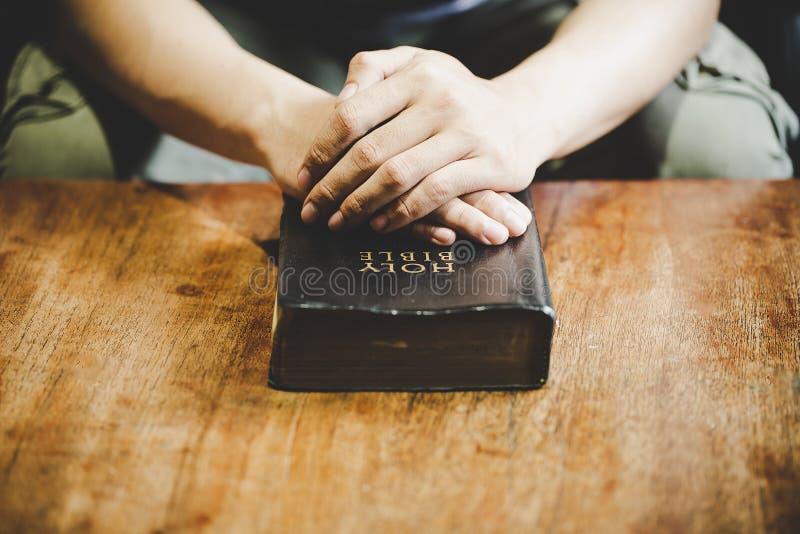Τα χέρια δίπλωσαν στην προσευχή σε μια ιερή Βίβλο στην έννοια εκκλησιών για την πίστη στοκ εικόνα