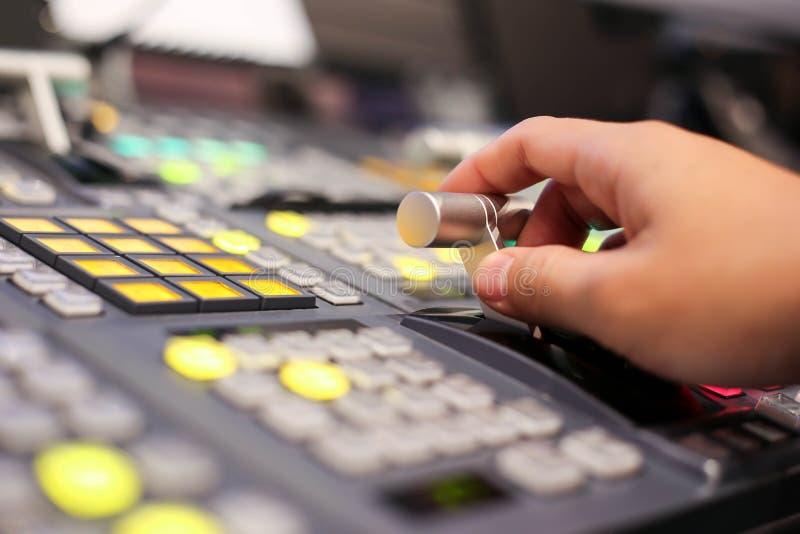 Τα χέρια διαλύουν επάνω Switcher των κουμπιών στο τηλεοπτικό κανάλι στούντιο, AUD στοκ φωτογραφία με δικαίωμα ελεύθερης χρήσης