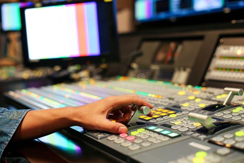 Τα χέρια διαλύουν επάνω Switcher των κουμπιών στο τηλεοπτικό κανάλι στούντιο, Audi στοκ φωτογραφίες