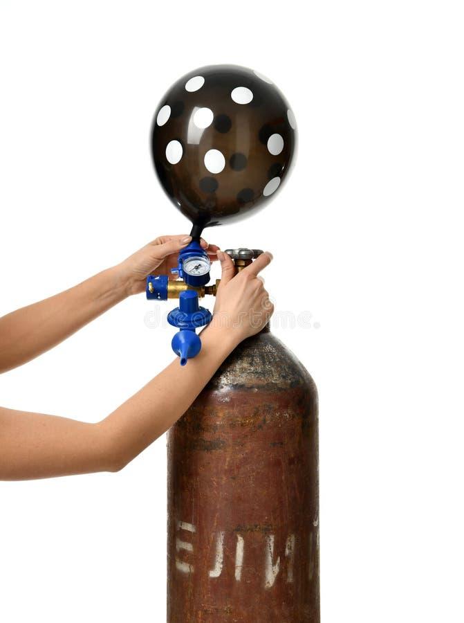 Τα χέρια διογκώνουν τη μαύρη διαστιγμένη δεξαμενή ηλίου χρήσης μπαλονιών με το ρυθμιστή οικονομίας γεμίζουν τη βαλβίδα στοκ φωτογραφία με δικαίωμα ελεύθερης χρήσης