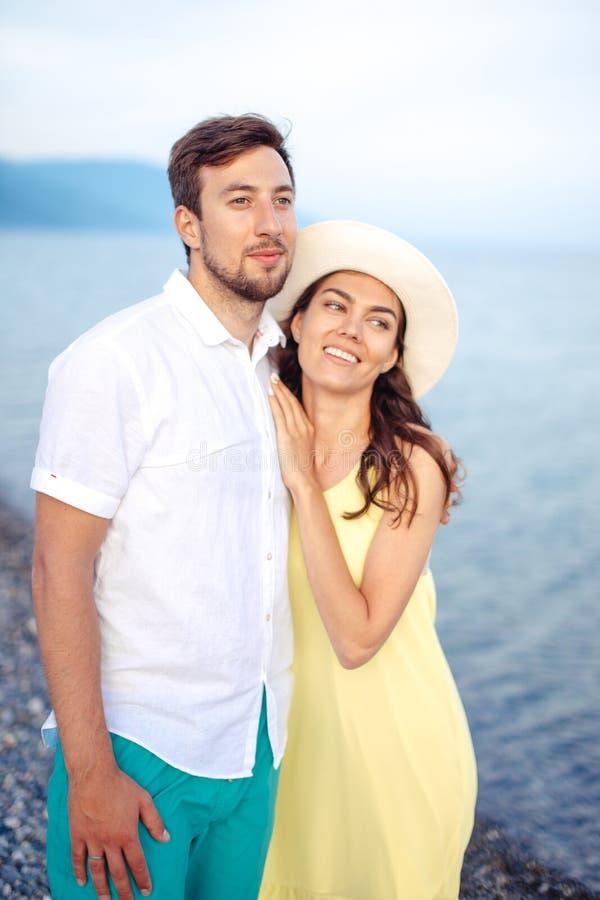 Τα χέρια εκμετάλλευσης ζεύγους στην παραλία και τον περίπατο και απολαμβάνουν από κοινού στοκ εικόνα