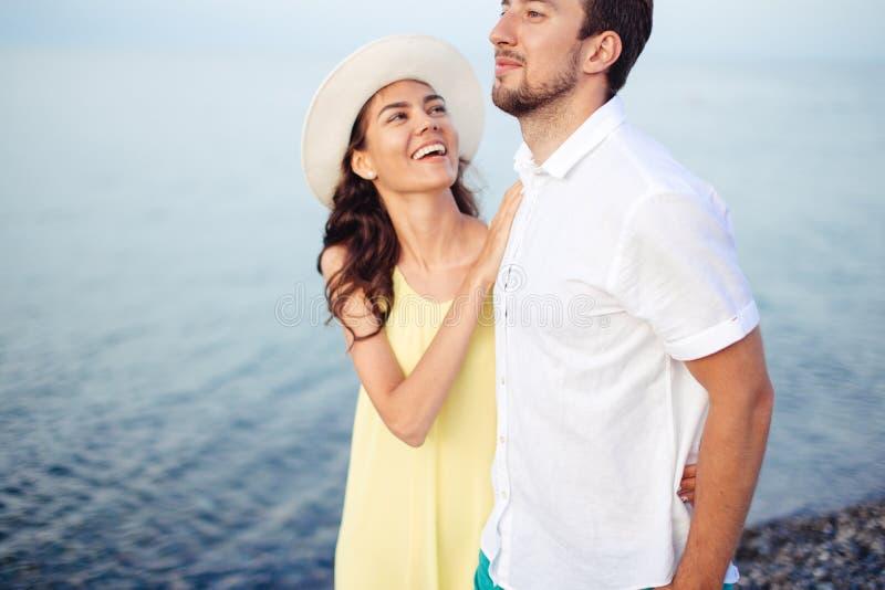 Τα χέρια εκμετάλλευσης ζεύγους στην παραλία και τον περίπατο και απολαμβάνουν από κοινού στοκ φωτογραφία