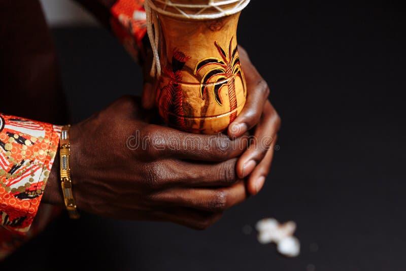 Τα χέρια ενός Αφρικανού με εθνική ενδυμασία κρατούν ένα τύμπανο τυμπάνου περικυκλωμένο από κοχύλια στοκ φωτογραφία με δικαίωμα ελεύθερης χρήσης