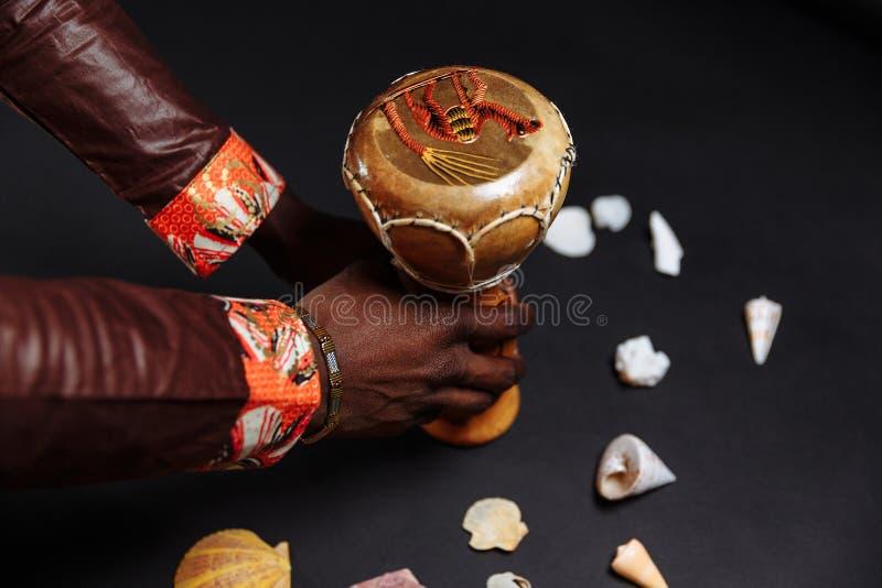 Τα χέρια ενός Αφρικανού με εθνική ενδυμασία κρατούν ένα τύμπανο τυμπάνου περικυκλωμένο από κοχύλια στοκ εικόνα με δικαίωμα ελεύθερης χρήσης