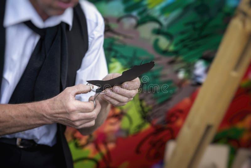 Τα χέρια ενός καλλιτέχνη οδών αποκόπτουν το ψαλίδι από ένα μαύρο σχεδιάγραμμα εγγράφου ενός κοριτσιού, πραγματική αστική σκηνή στοκ εικόνα με δικαίωμα ελεύθερης χρήσης