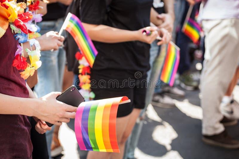 Τα χέρια ενός κοριτσιού που κρατά ένα smartphone τηλεφωνούν με μια κάμερα και μια ομοφυλοφιλική σημαία ουράνιων τόξων κατά τη διά στοκ φωτογραφία
