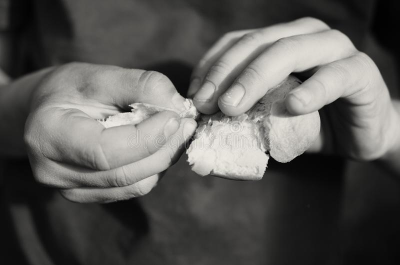 Τα χέρια ενός πεινασμένου αγοριού επαιτών κρατούν και σπάζουν ένα κομμάτι του ψωμιού στοκ φωτογραφία