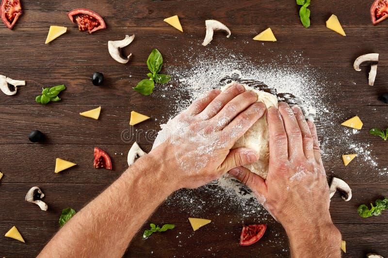 Τα χέρια ζυμώνουν τη ζύμη για την κατασκευή πιτσών στοκ εικόνα