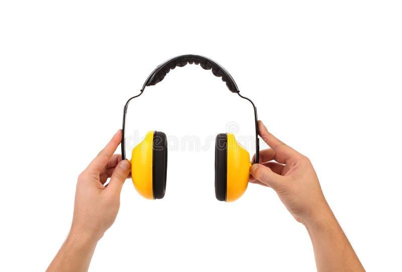 Τα χέρια κρατούν τα λειτουργώντας προστατευτικά ακουστικά. στοκ φωτογραφίες