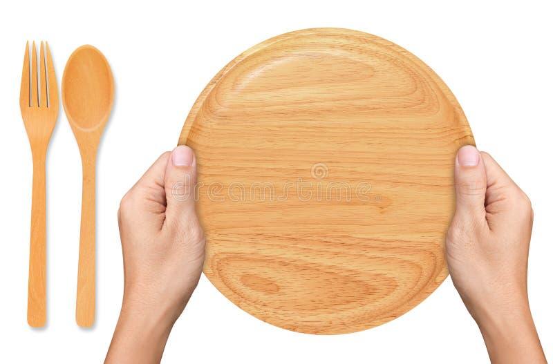 Τα χέρια κρατούν το κενό ξύλινο πιάτο στο λευκό στοκ φωτογραφία με δικαίωμα ελεύθερης χρήσης
