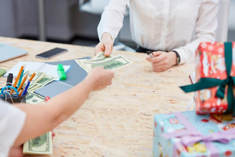 Τα χέρια μεταφέρουν τα χρήματα σε άλλη κινηματογράφηση σε πρώτο πλάνο χεριών στο υπόβαθρο ενός πίνακα με τα δώρα στοκ εικόνες