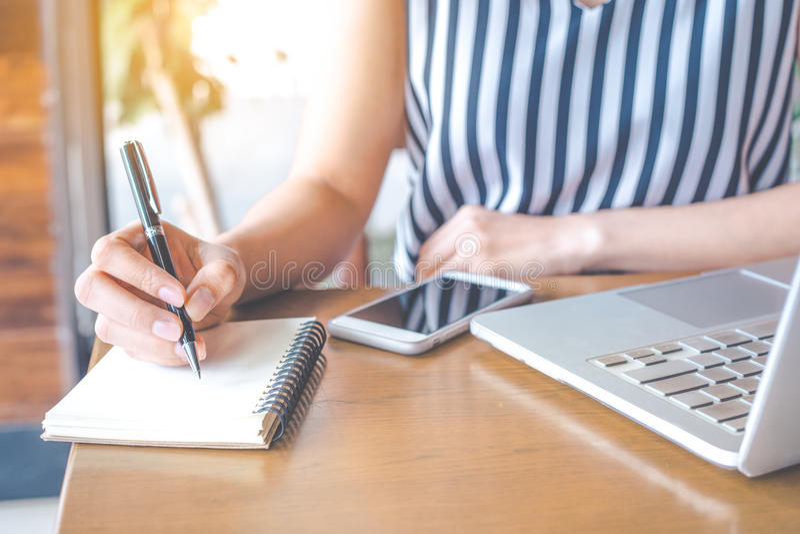 Τα χέρια μιας επιχειρησιακής γυναίκας που εργάζεται σε έναν υπολογιστή και ένα γράψιμο στοκ εικόνες με δικαίωμα ελεύθερης χρήσης