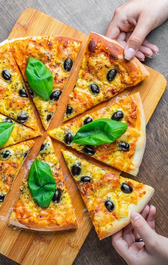 Τα χέρια παίρνουν μια φέτα της πίτσας με το τυρί μοτσαρελών, τις ντομάτες, το πιπέρι, την ελιά, τα καρυκεύματα και το φρέσκο βασι στοκ φωτογραφία