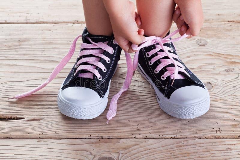 Τα χέρια παιδιών εμπλέκουν τις δαντέλλες παπουτσιών στοκ εικόνα με δικαίωμα ελεύθερης χρήσης