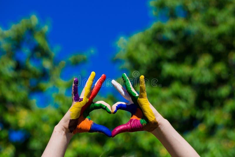 Τα χέρια παιδιών που χρωματίζονται στα φωτεινά χρώματα κάνουν μια μορφή καρδιών στο υπόβαθρο θερινής φύσης στοκ φωτογραφία