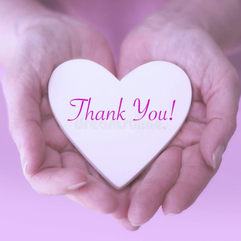 Τα χέρια της γυναίκας που κρατούν την άσπρη καρδιά με τις λέξεις σας ευχαριστούν στοκ εικόνες