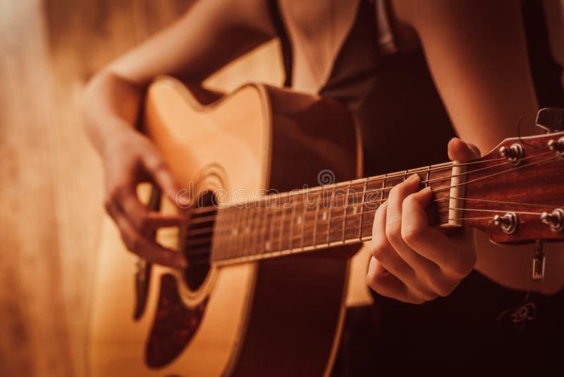Τα χέρια της γυναίκας που παίζουν την ακουστική κιθάρα, κλείνουν επάνω στοκ φωτογραφίες