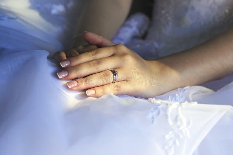 Τα χέρια της νύφης στο φόντο ενός ενδύματος στοκ εικόνα με δικαίωμα ελεύθερης χρήσης