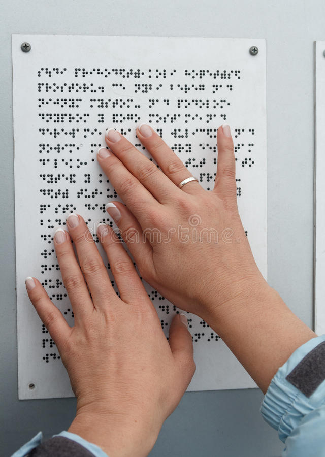 Τα χέρια της που διαβάζουν τον πίνακα μπράιγ στοκ εικόνα