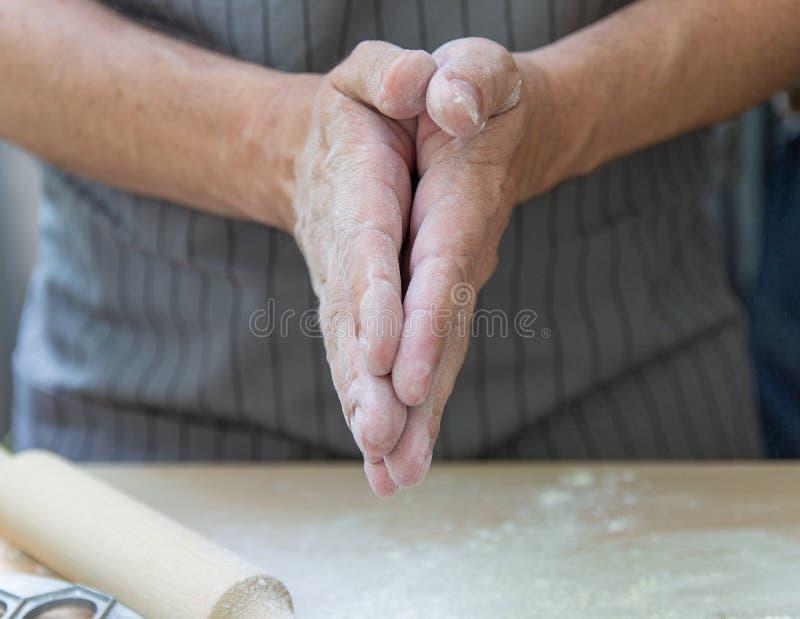 Τα χέρια του αρχιμάγειρα ζυμώνουν τη ζύμη σε έναν ξύλινο πίνακα στοκ εικόνες