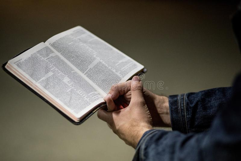 Τα χέρια του ενήλικου αρσενικού που κρατούν ένα ανοιγμένο βιβλίο και με τα δύο παραδίδουν μια πυγμή με ένα γκρίζο συγκεκριμένο υπ στοκ φωτογραφία με δικαίωμα ελεύθερης χρήσης