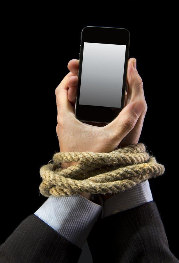 Τα χέρια του επιχειρηματία έθισαν στους κινητούς καρπούς δεσμών τηλεφωνικών σχοινιών στον εθισμό Διαδικτύου smartphone στοκ εικόνα