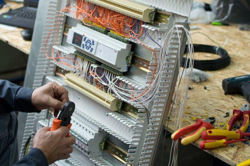 Τα χέρια του ηλεκτρικού τεχνικού που συγκεντρώνει τη χαμηλή τάση βιομηχανικό HVAC ελέγχουν το θαλαμίσκο στο εργαστήριο Φωτογραφία στοκ φωτογραφίες