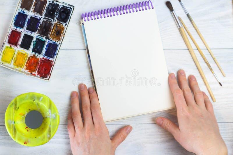 Τα χέρια του καλλιτέχνη, βούρτσες παλετών χρωμάτων, διαφορετικά χρώματα Το κορίτσι σύρει Τα εργαλεία του καλλιτέχνη για την πραγμ στοκ εικόνες με δικαίωμα ελεύθερης χρήσης