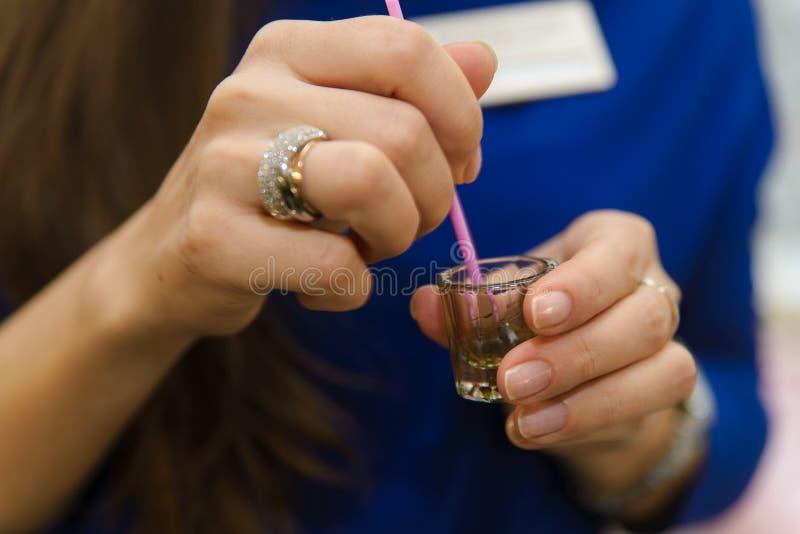 Τα χέρια του καλλιτέχνη beautician- makeup εφαρμόζουν henna χρωμάτων, σχέδιο, τακτοποιημένα φρύδια σε ένα σαλόνι ομορφιάς στη διό στοκ εικόνα