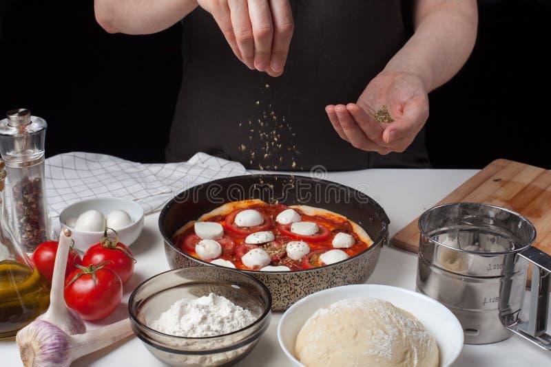 Τα χέρια του μάγειρα γυναικών ψεκάζουν το ιταλικό ακατέργαστο oreano της Μαργαρίτα πιτσών σε ένα σκοτεινό υπόβαθρο Στον άσπρο πίν στοκ φωτογραφία