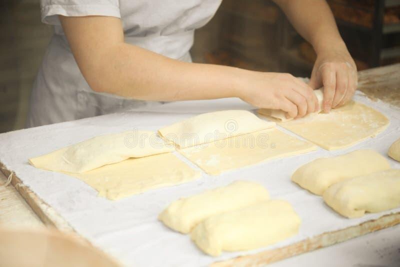 Τα χέρια του μάγειρα ζυμώνουν ήπια τη ζύμη Λίγο οικογενειακό αρτοποιείο στοκ φωτογραφία με δικαίωμα ελεύθερης χρήσης