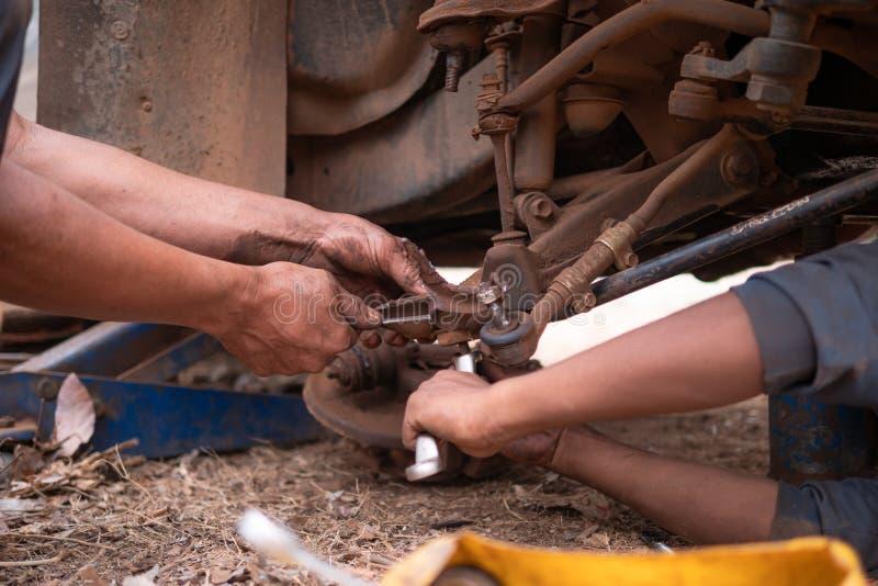 Τα χέρια του μηχανικού wishbone καθορισμού βραχίονα ελέγχου του μέρους φορτηγών στην επισκευή αντιμετωπίζουν τη ρόδα στοκ φωτογραφίες