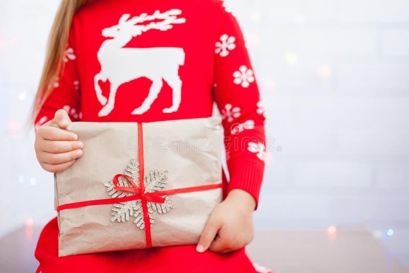 Τα χέρια του μικρού κοριτσιού κρατούν το δώρο Χριστουγέννων στοκ φωτογραφία