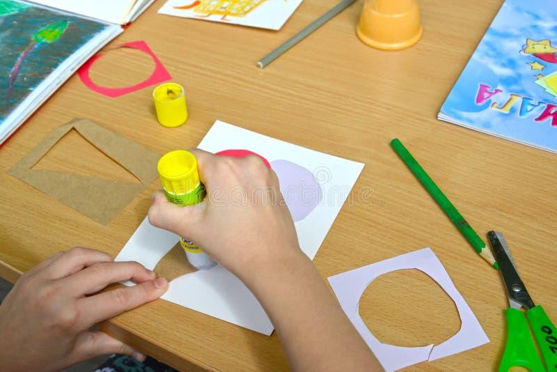 Τα χέρια του παιδιού κολλούν μια λεπτομέρεια εγγράφου Κύρια κατηγορία παιδιών στο έγγραφο applique στοκ φωτογραφία με δικαίωμα ελεύθερης χρήσης