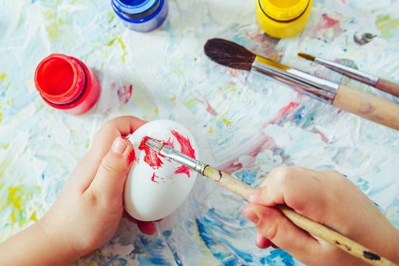 Τα χέρια του παιδιού κρατούν μια βούρτσα με το κόκκινο χρώμα και το αυγό χρωμάτων μέχρι Πάσχα, στενός ένας επάνω στοκ φωτογραφία