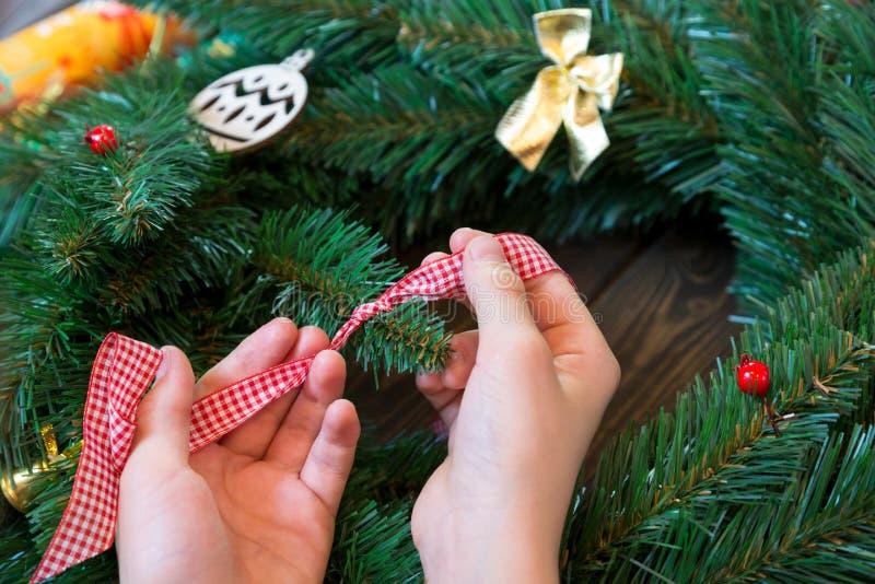 Τα χέρια του παιδιού κρατούν την κόκκινη και άσπρη κορδέλλα για τη διακόσμηση του στεφανιού Χριστουγέννων στοκ εικόνες