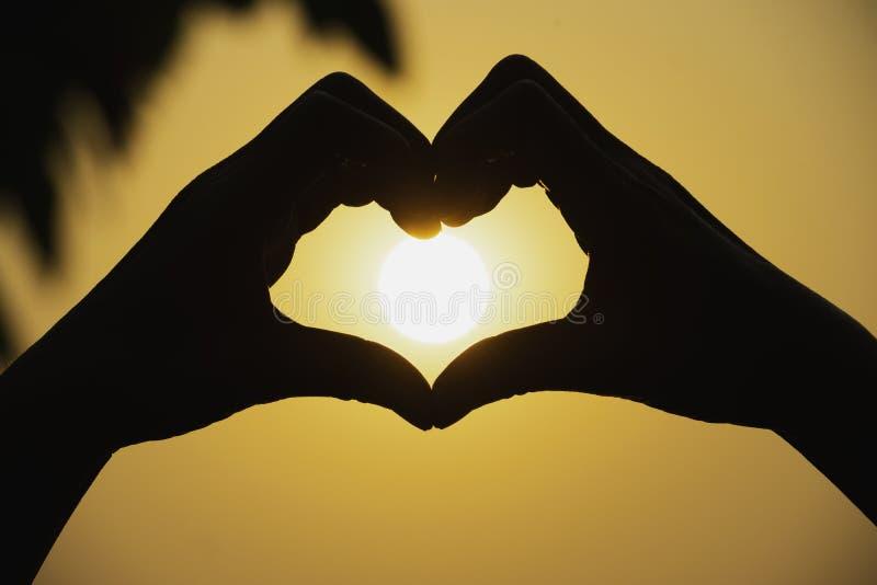 Τα χέρια του προσώπου κάνουν την καρδιά από το δάχτυλο στο υπόβαθρο ηλιοβασιλέματος σκιαγραφιών στοκ φωτογραφία με δικαίωμα ελεύθερης χρήσης