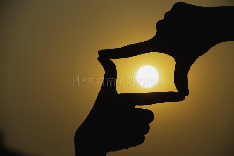 Τα χέρια του προσώπου κάνουν την καρδιά από το δάχτυλο στο υπόβαθρο ηλιοβασιλέματος σκιαγραφιών στοκ εικόνα