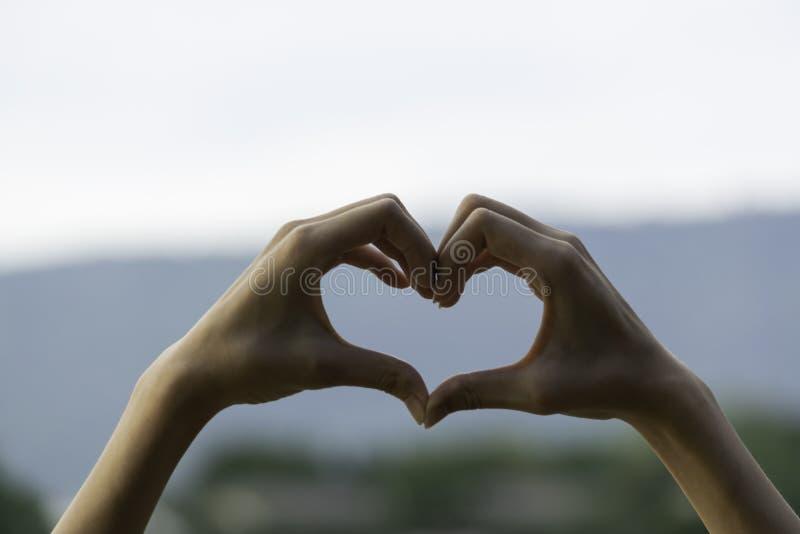 Τα χέρια του προσώπου κάνουν την καρδιά από το δάχτυλο στο υπόβαθρο ηλιοβασιλέματος σκιαγραφιών στοκ φωτογραφίες με δικαίωμα ελεύθερης χρήσης