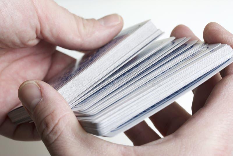 Τα χέρια των ατόμων μεταθέτουν μια γέφυρα των καρτών στοκ εικόνα με δικαίωμα ελεύθερης χρήσης