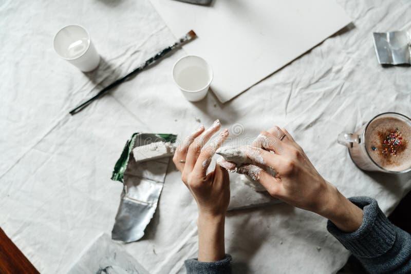 Τα χέρια των γυναικών φορμάρουν τη μορφή σε μια κατηγορία για την παραγωγή των πραγμάτων αργίλου στοκ φωτογραφίες