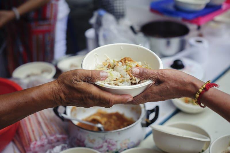 Τα χέρια των εθελοντών εξυπηρετούν τα ελεύθερα τρόφιμα φτωχός και ενδεής στην πόλη: Οι φτωχοί άνθρωποι φέρνουν ένα εμπορευματοκιβ στοκ εικόνα