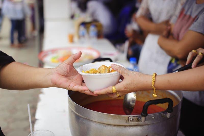 Τα χέρια των εθελοντών εξυπηρετούν τα ελεύθερα τρόφιμα φτωχός και ενδεής στην πόλη: Οι φτωχοί άνθρωποι φέρνουν ένα εμπορευματοκιβ στοκ εικόνες